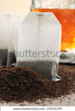 Tea bags and dried tea leaves with  prepared tea in the background.   Macro still life with shallow dof.