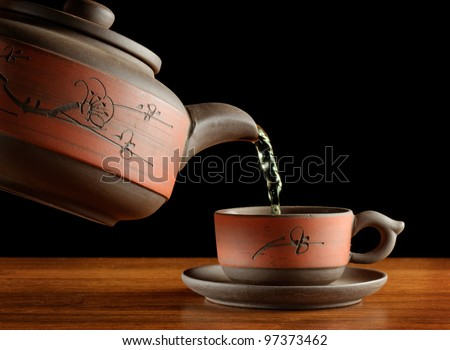 tea being poured from kettle in cup, all in asian style , black background