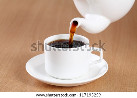 Tea being poured into tea cup on table.