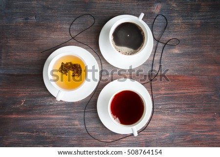 Tea, black tea, green tea, black espresso coffee in white porcelain cups on rustic wooden table. Top view. Copy space. Special light.