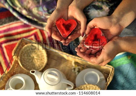 tea Ceremony. Two cakes in the shape of a heart on male and female hands