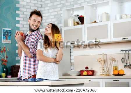 Tea ceremony. Young couple in love drinking hot tea while standing and cooking in the kitchen clamps to each other and laughing at each other