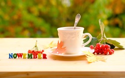 tea, coffee in a mug on the table in the garden, colored letter words, the concept of outdoor tea drinking, good weather, a cozy autumn mood