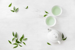 Tea concept, two white cups of tea and teapot surrounded with green tea leaves, view from above, space for a text
