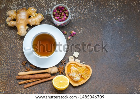 Tea, Cup of tea, dried tea leaves with tea pot and herb, honey,ginger on old kitchen table.