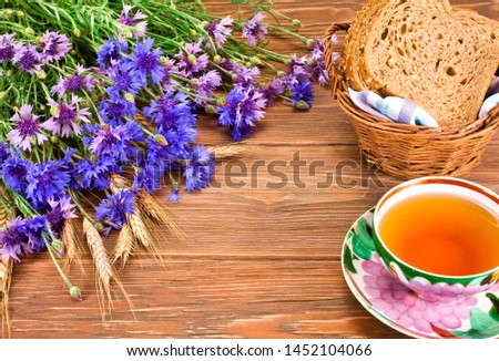 Tea cup with basket of bread, cornflowers and ears on a wooden background. Copy space. #1452104066