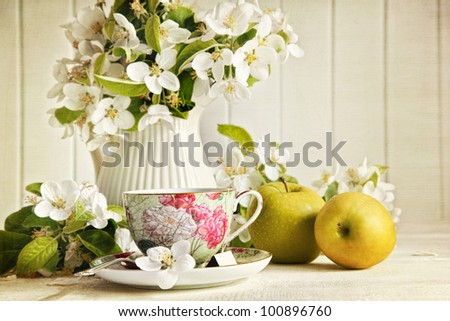 Tea cup with fresh flower blossoms and green apples