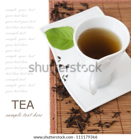 Tea cup with green leaf on the mat isolated on white background with sample text