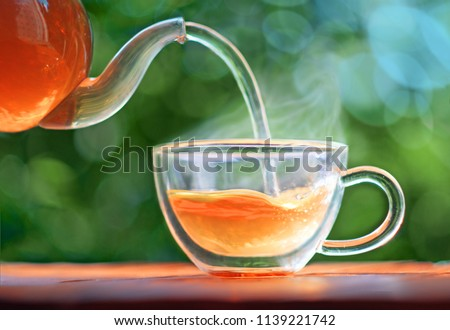 Tea cup with hot tea and tea pot.