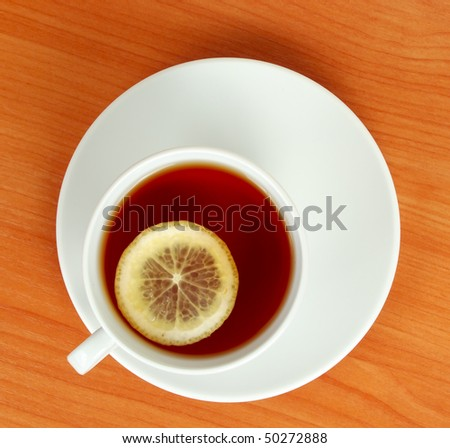 tea cup with lemon on wooden table from above