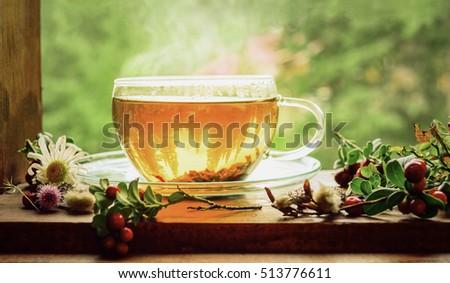 Tea cup with tea leaves on window.