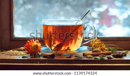 Tea cup with tea leaves on window. Tea time.