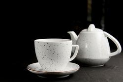 Tea cup with tea pot over black background. Tea time close up.