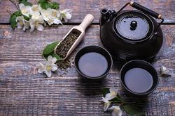 Tea cups, tea pot, green tea and sprigs of jasmine flowers on wooden background. Top view.