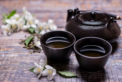 Tea cups with hot drink, tea pot, green tea leaf and jasmine flowers on wooden background, place for text. Concept of freshly healthy drink.
