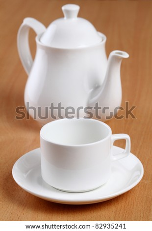tea cups with teapot on table.