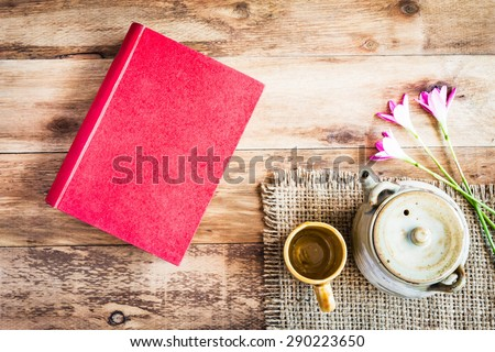 Tea cups with teapot with red book on old wooden table. Top view.