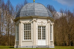 Tea dome or Theekoepel or Gloriette with its square windows and gray dome with bare trees in the background, sunny spring day at Paleispark Kroondomein Het Loo in Apeldoorn, Netherlands