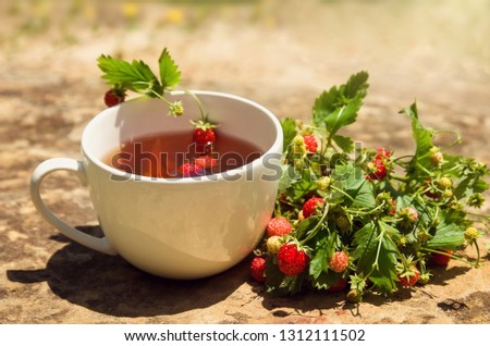 Tea drink in white Cup with wild wild wild strawberry berry on yellow stone background, scented Breakfast #1312111502