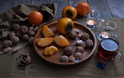 tea drink on the table, whole and sliced persimmons on a wooden tray, walnuts, a candle is burning nearby and decorations on a green background