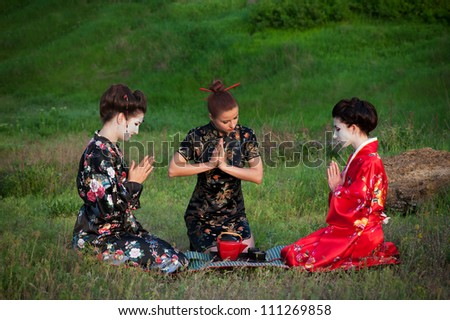 Tea drinking. Asian style portrait of three woman sitting on the grass and drinking tea