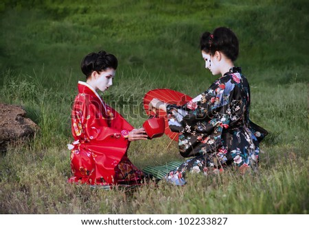 Tea drinking. Asian style portrait of two woman sitting on the grass and drinking tea