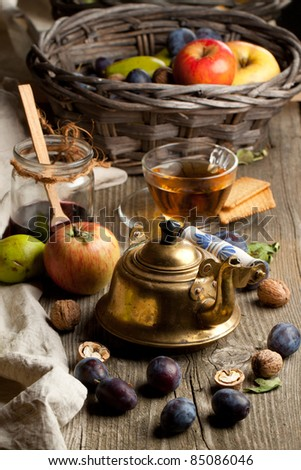 Tea drinking with fresh various fruits, old golden teapot and glass jar of jam in old wooden table
