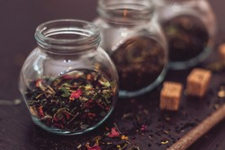 Tea flavors, dried herbs in small jars on a dark background, brown sugar