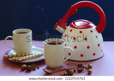 tea for two, two mugs with warm tea, tea kettle with red dots, little snack and acorns to set autumn mood, prepared for nice pause of couple of friends (picture with copy space for text or quotes)