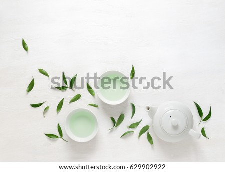 Shutterstock Tea freshly brewed in a teapot and two cups, surrounded with fresh tea leaves, top view composition, space for a text