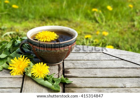 tea from dandelion  in a rustic earthenware cup on a wooden table against a blurred meadow with copy space, selected focus, narrow depth of field #415314847