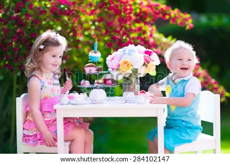 Tea garden party for kids. Child birthday celebration. Little boy and girl play outdoor drinking hot chocolate and eating cake. Children eat sweets. Kid event with toy dish and flower decoration.