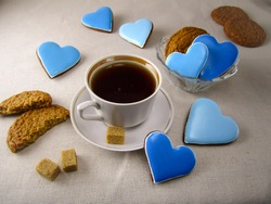 Tea in a cup with blue heart cookies on the table