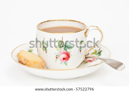 Tea in antique cup with saucer and spoon with biscuits on the side