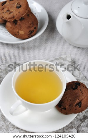 Tea in cup, sweet chocolate chip cookies and teapot