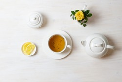 tea in cup with saucer, teapot, sugar bowl, yellow rose in milk jug and lemon on white background