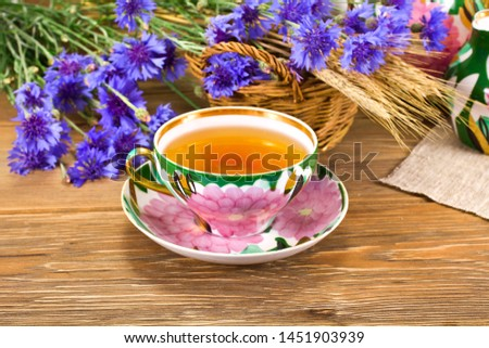 Tea in cup with the cornflowers and wheat ears on a wooden background. #1451903939