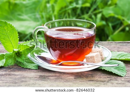 tea in glass cup and mint on wooden table