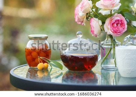 Photo of  Tea in glass teapot. Romantic lunch in the garden. Summer time. Close up