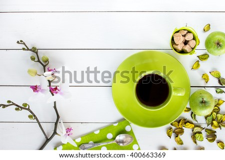 Stock Photo tea in green cup,  orchid flower, ripe apples, dry decor, cane sugar in baby bucket, napkin at white polka dots on white painted wooden table, top view