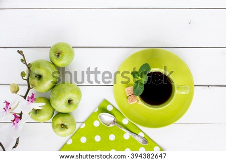 Stock Photo tea in green cup, tea spoon, cane sugar,  ripe green apples, orchid flower,  green napkin at white polka dots on white painted wooden table, top view