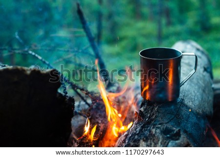 Tea in metal mug heats up on stone on bonfire. Hot drink on nature. Tea drinking in open air. Camping in dusk. Romantic warm atmosphere outdoor in twilight . Active rest.