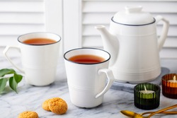 Tea in mugs with teapot on marble background. Close up.