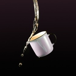 tea in the air pours into a cup. tea splash on blackbackground. cup of tea in the air