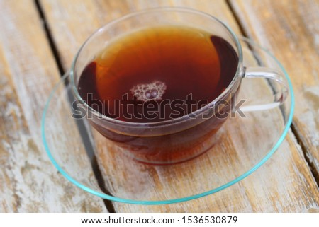 Tea in transparent cup on transparent saucer on rustic wooden surface  #1536530879