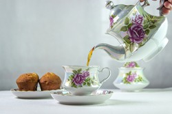 Tea is poured into a cup. A cup of tea on a white tablecloth. Light breakfast. White tea set with flowers.