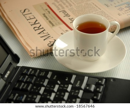 Tea, laptop and business newspaper