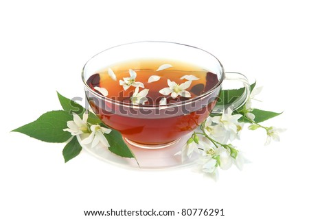 Tea leaves with fresh jasmine flowers and glass cup on white background