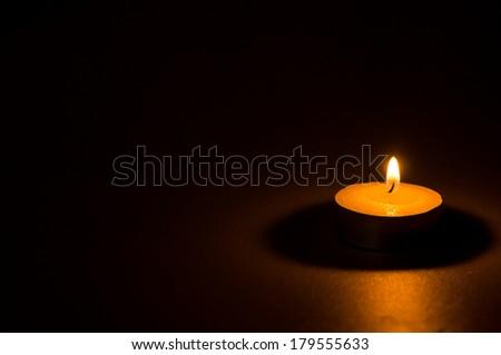 Tea light candle on black background #179555633