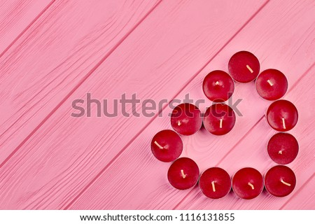 Tea light candles forming heart shape. Heart shape made of red scented candles on pink wooden background with copy space, top view. #1116131855